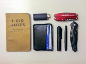 A small collection of items that can fit in a pocket, including Notes notebook, pen, Leatherman tool, lighter, and wallet